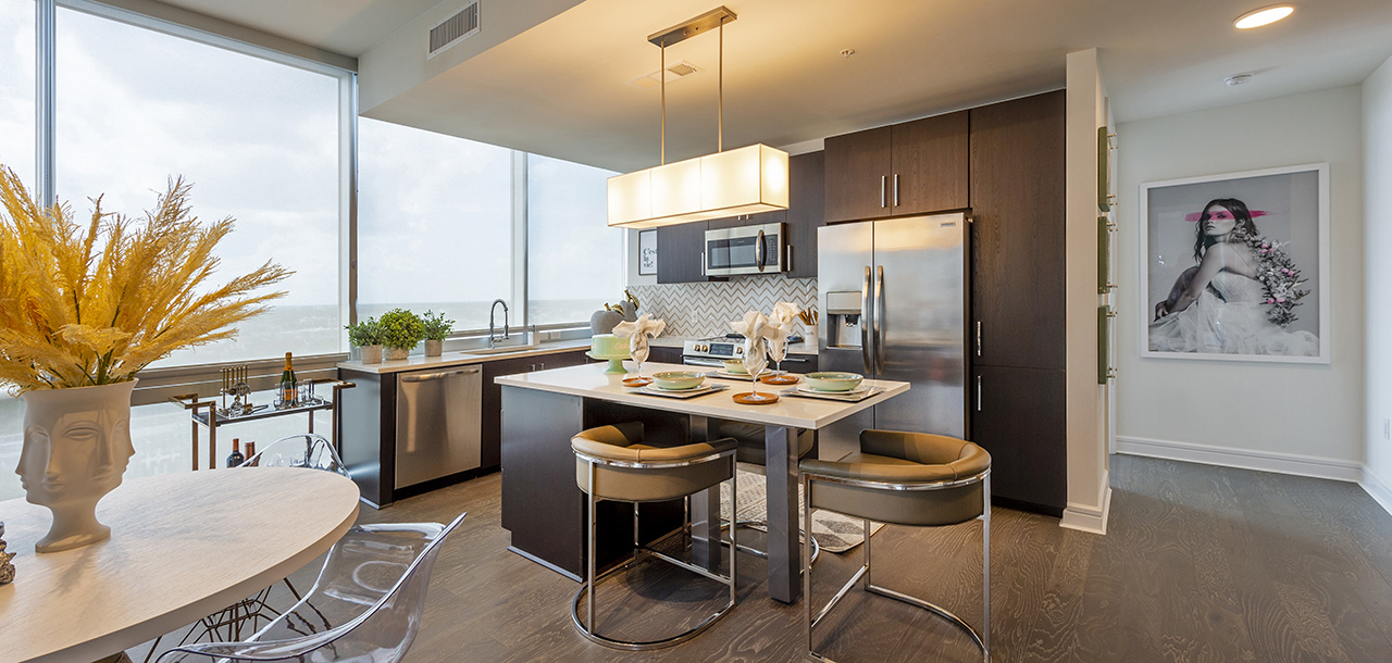 Kitchen with wood floor and cabinets, light counters, stainless steel appliances, modern furniture and artwork.