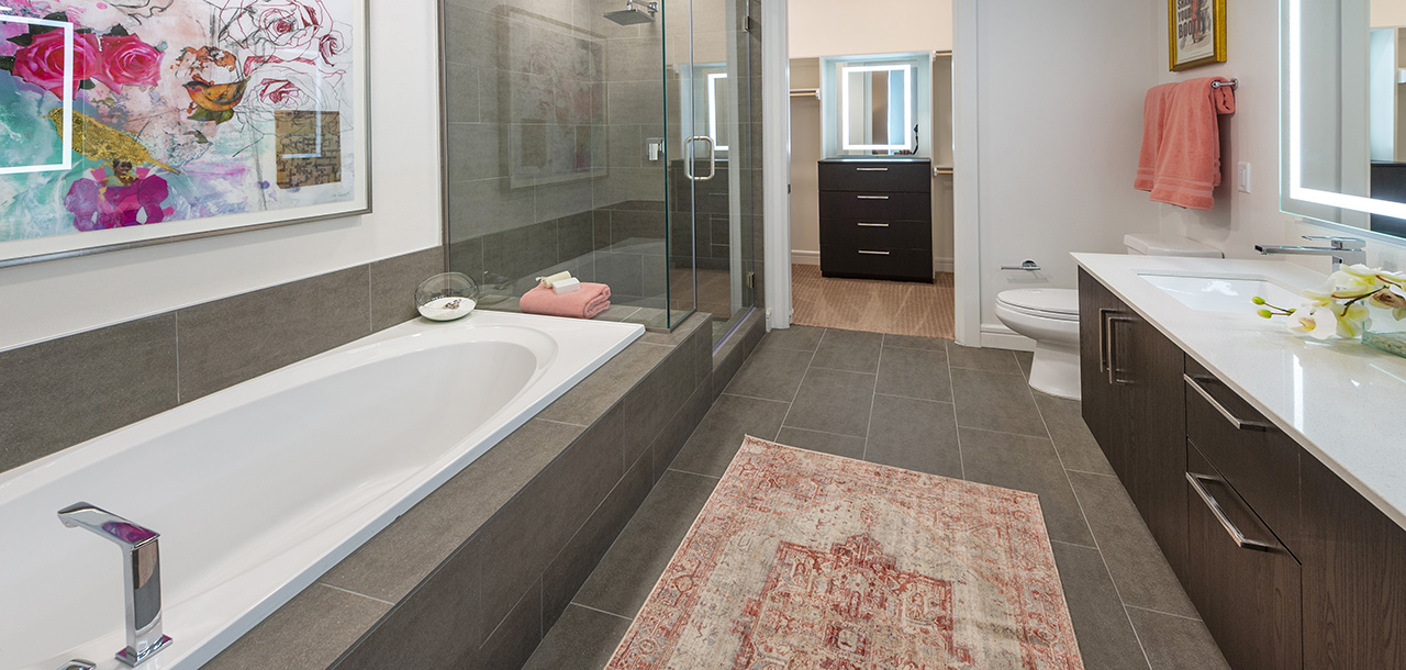 Bathroom with tile floor, built in tub and shower with glass walls, wood cabinets, and smooth white counter.