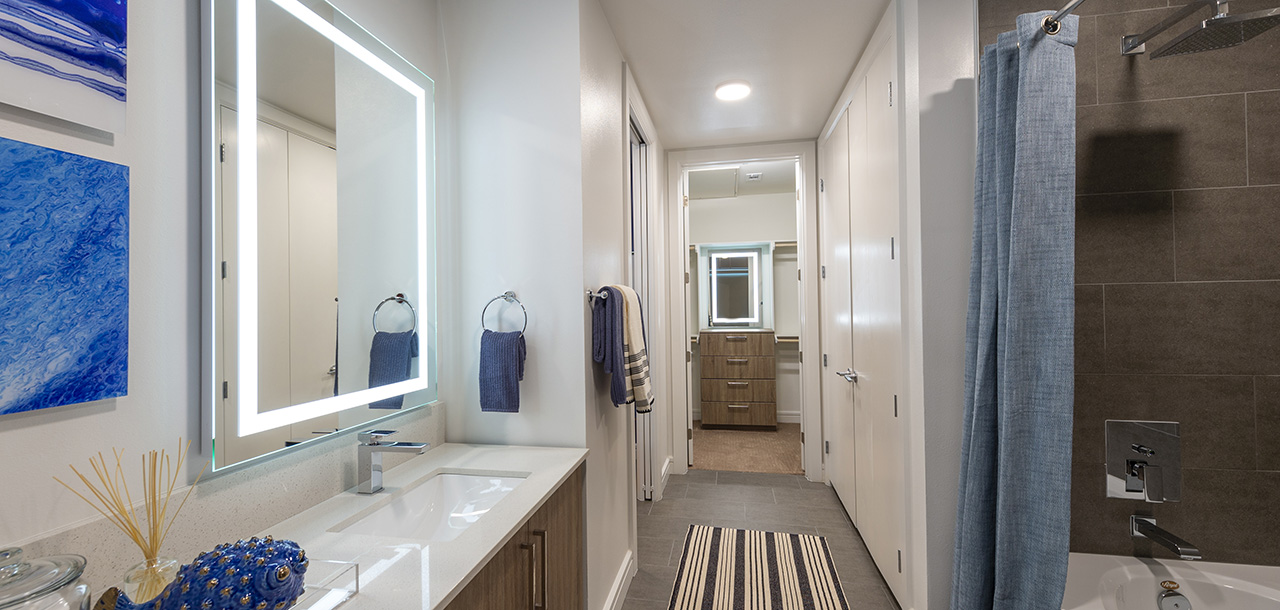 Bathroom with tile floor, wood cabinets, light counter, and large tiled shower tub with curtain.