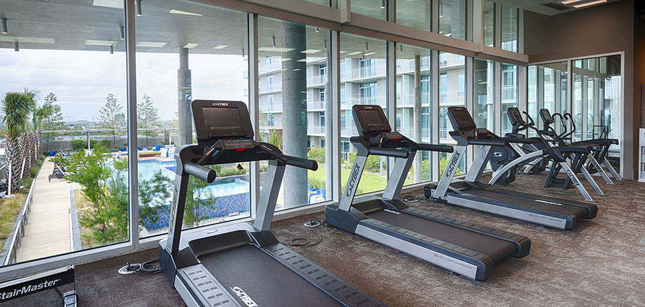 Fitness center with carpet floors, row of treadmills, and large windows overlooking pool area.