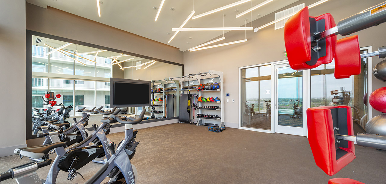 Fitness center with large mirror wall, wall mounted TV, carpet floor, and exercise equipment.